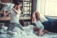 Darum solltest du den Kopfkissenbezug regelmäßig waschen: Mann und Frau haben eine Kissenschlacht