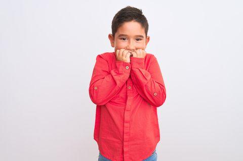 Peinlich berührtes Kind in rotem Hemd