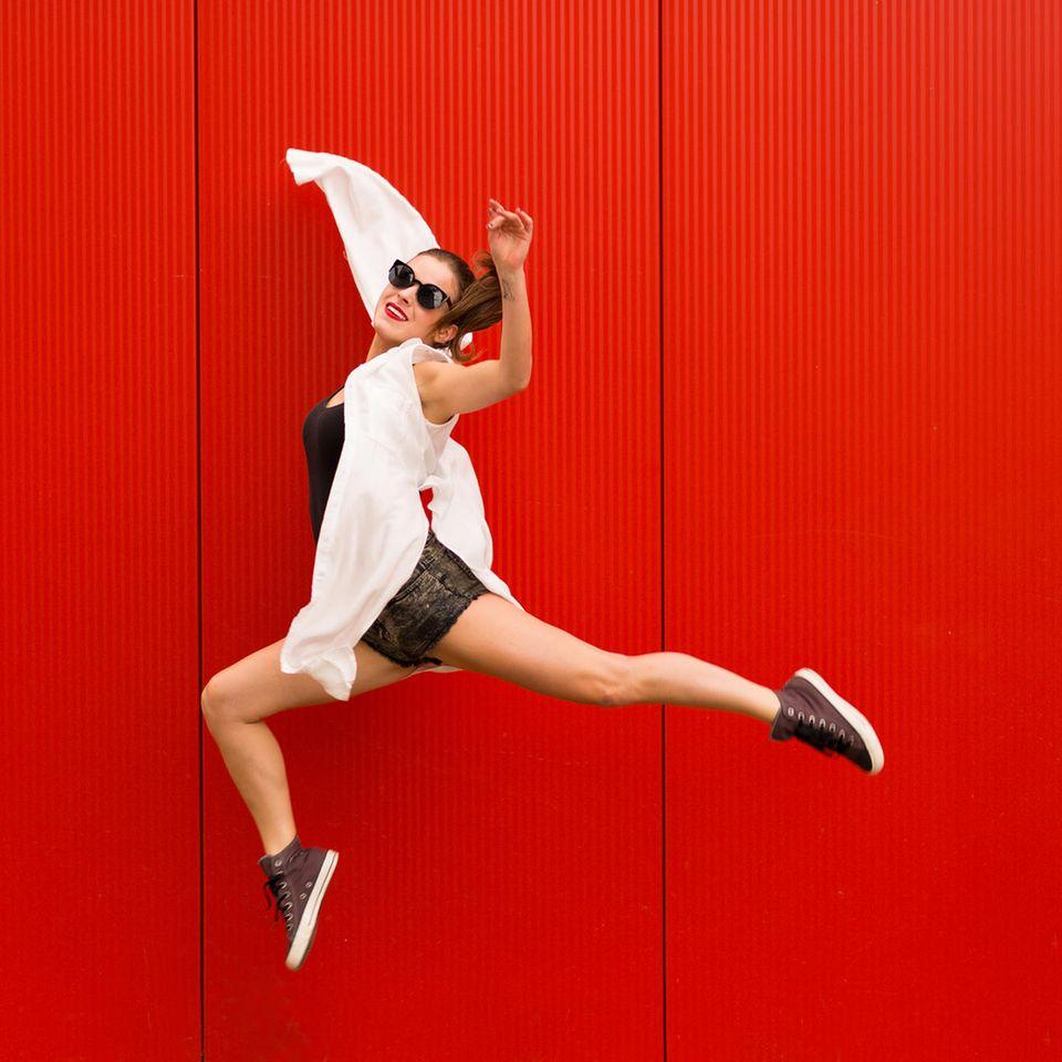 Junge Frau springt vor rotem Hintergrund in die Luft