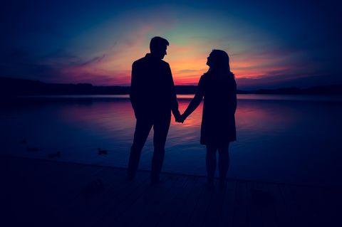Paar hält Händchen vor Sonnenuntergang