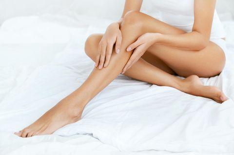 Frau streicht sich über die Beine