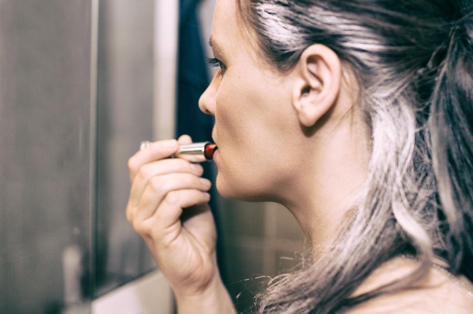 Graue Haare: Frau mit grauen Haaren trägt Lippenstift auf