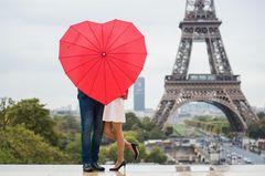 Städtereisen für Verliebte: Ein Pärchen küsst sich vor dem Eiffelturm