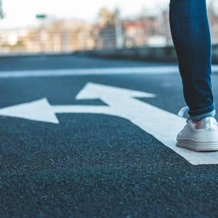 Multitasking schwächt die Willenskraft: Eine Frau geht über einen Pfeil auf dem Asphalt