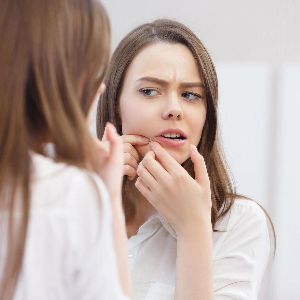 Hausmittel gegen Akne: Frau vor Spiegel