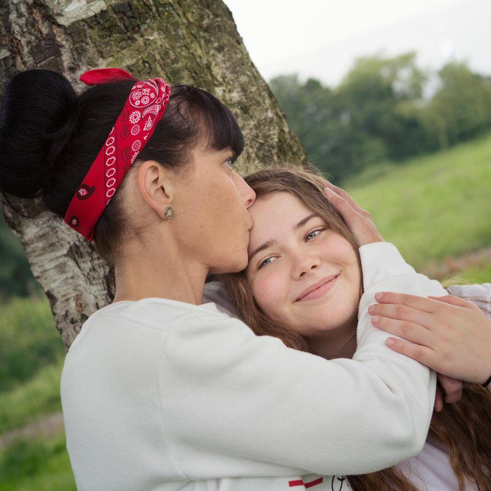 Warum sind Fische so gute Mütter? Eine Frau küsst ihre Tochter auf den Kopf