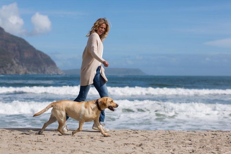 Wechseljahresbeschwerden lindern: Das hat geholfen: Frau mit Hund am Strand