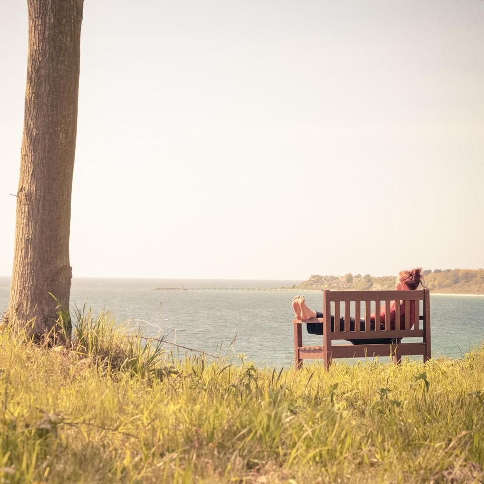 Lust aufs Verzichten: Ausbruch aus der Tretmühle: Frau sitzt auf Bank am Wasser