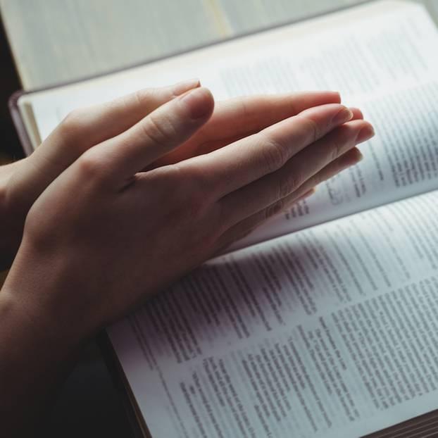 Jehovas Zeuge: Betende Hände über einem Buch