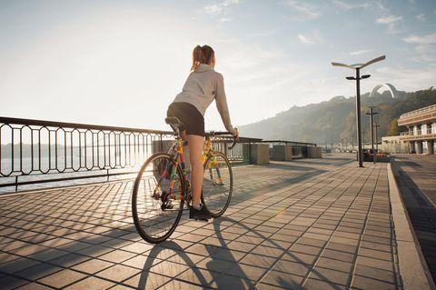Frau mit Rennrad auf Promenade