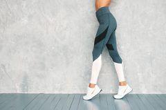 Frau in Sportkleidung vor Wand