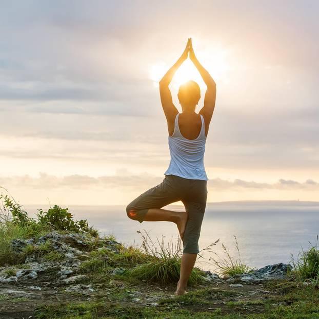 Frau in Yogastellung an Küste
