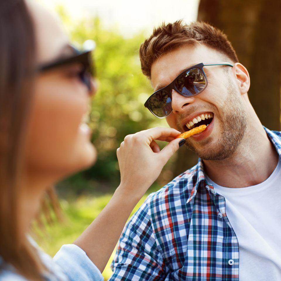Frau füttert Mann mit Pommes