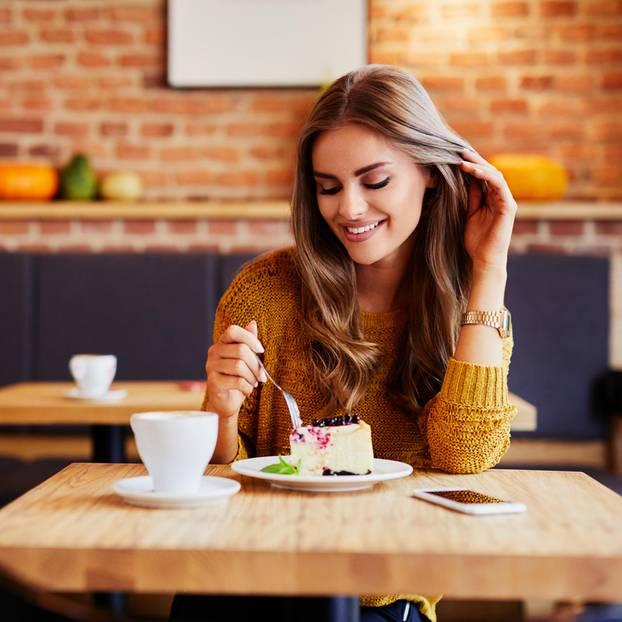 Frau im Cafe mit Kaffee und Kuchen