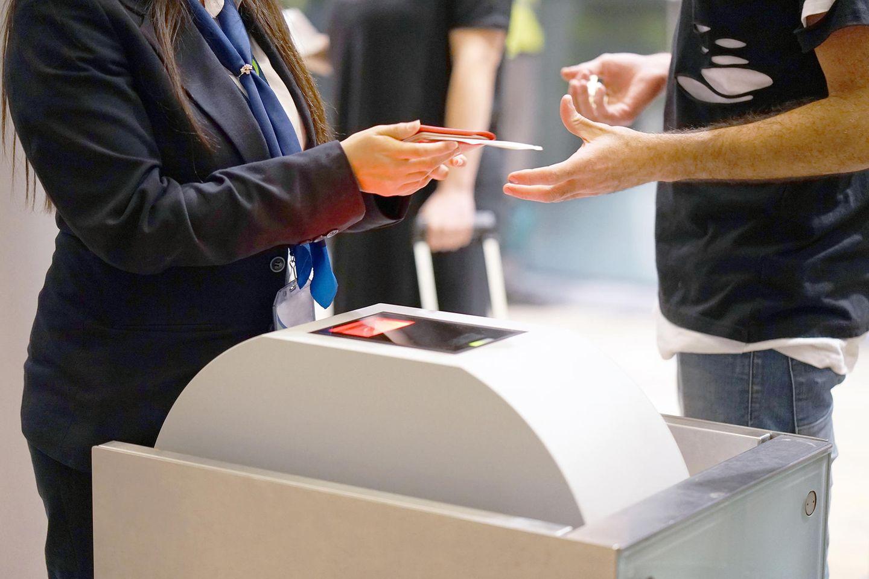 Frau kontrolliert Pass am Flughafen