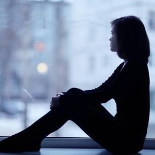 Frau sitzt am Fenster und schaut raus