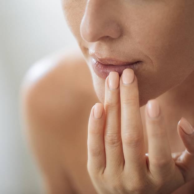 Spröde Lippen: Frau fasst sich an die Lippen
