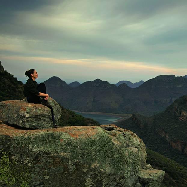 Drakensberge: Südafrika-Safari mal anders: Frau sitzt auf Stein vor bergiger Kulisse