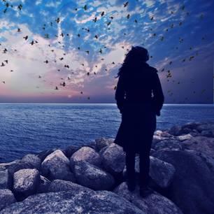 Frau blickt auf Sonnenuntergang über Meer
