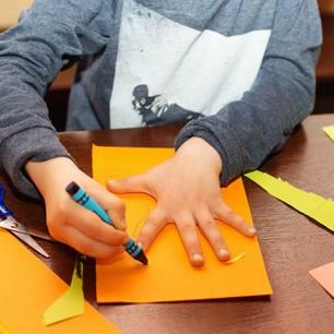 Kind zeichnet seine Hand ab