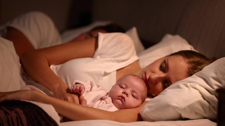 Mutter schläft mit Baby im Bett