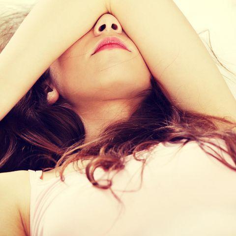 Testosteronmangel bei Frauen: Frau legt Arm über den Kopf