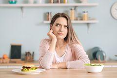 Blähende Lebensmittel: Frau sitzt zwischen Salat und Burger