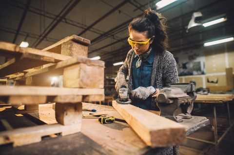 Schreinerin bearbeitet ein Stück Holz.