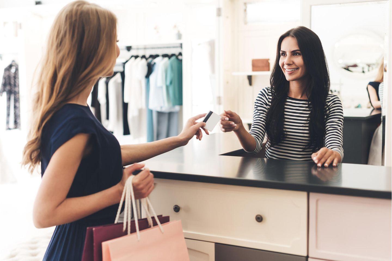 Verkäufer: Verkäuferin nimmt die Kreditkarte ihrer Kundin entgegen.