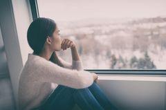 Burnout. Traurige Frau am Fenster