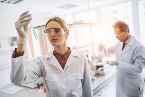 Chemiker: Chemikerin untersucht ein Reagenzglas mit Chemikalien