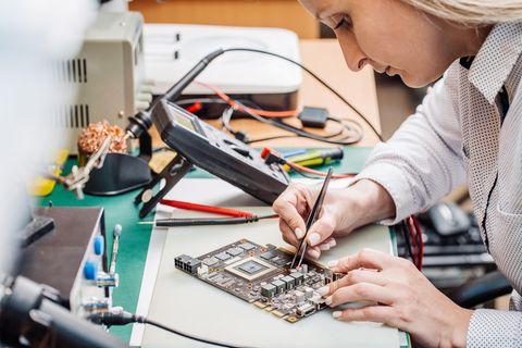 Elektrotechniker: Elektrotechnikerin arbeitet an einem Computerteil
