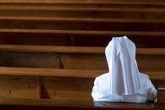 Nonne sitzt auf Bank in Kirche