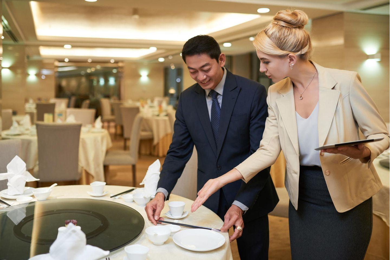 Eventmanager: Eine Eventmanagerin bespricht die Tischdeko mit dem Restaurantbetreiber.