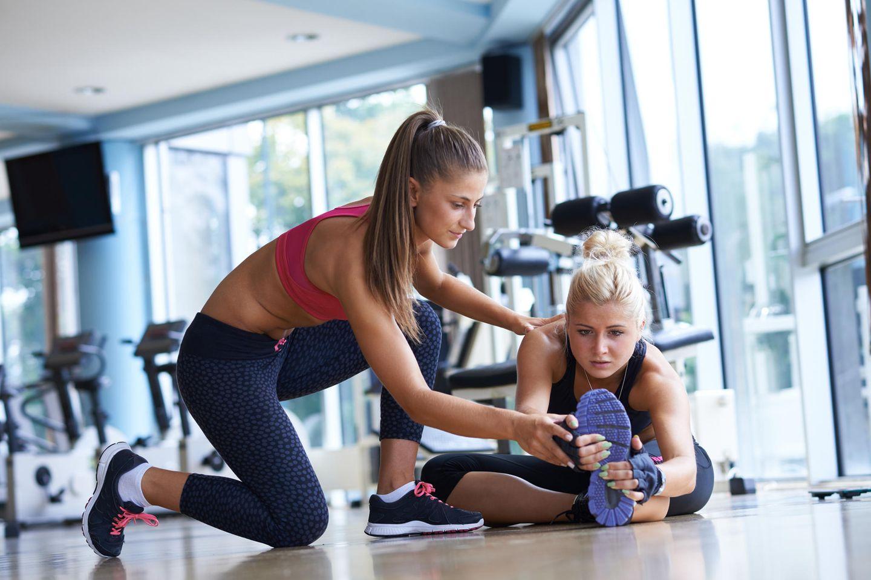 Fitnesstrainer: Fitnesstrainerin unterstützt eine junge Frau beim Dehnen