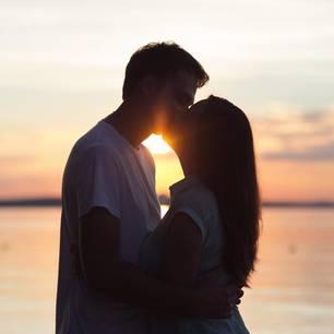 Horoskop: Ein Pärchen küsst sich am Strand bei Sonnenuntergang