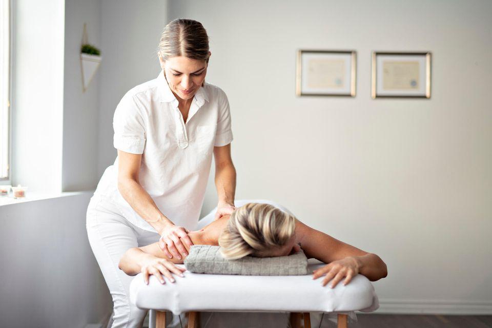 Masseur: Eine Masseurin behandelt den Rücken ihrer Patientin.