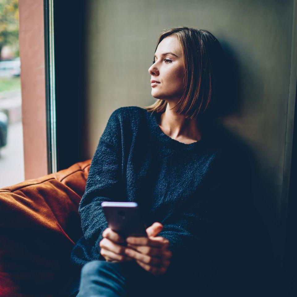 Was sollte man niemals schlecht gelaunt tun? Eine schlecht gelaunte Frau schaut nachdenklich aus dem Fenster