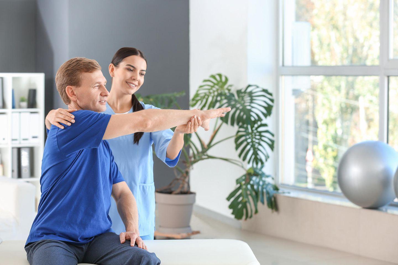 Physiotherapeutin hilft ihrem Patienten bei einer Armübung