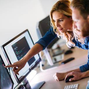Systemadministratorin hilft einem Mann bei seinem Computerproblem