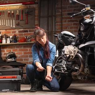 Junge Frau arbeitet in ihrer Werkstatt an einem Motorrad.