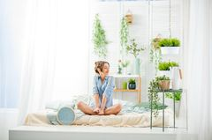 Exotische Zimmerpflanzen: Lust auf Monstera & Co.: Frau im Schneidersitz umgeben von Pflanzen