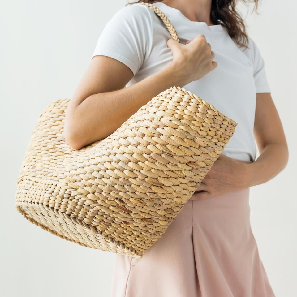 Grüner Knopf: Sozial und ökologisch produzierte Kleidung: Frau mit Korbtasche