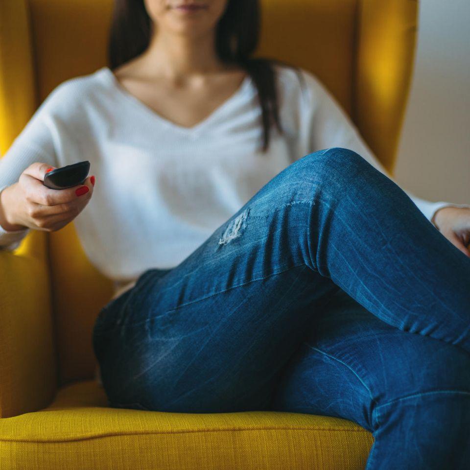 Digitale CO2-Bilanz: Fußabdruck von Netflix & Co.: Frau sitzt mit Fernbedienung auf Sessel