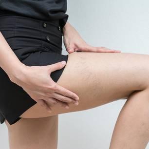Frau hebt ihr Bein auf dem Besenreiser sind