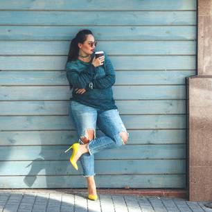 Frau mit Kaffee lehnt an blaue Holzwand