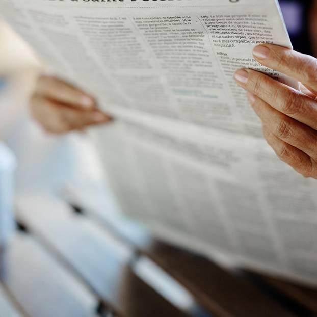 Ältere Frau liest Zeitung am Tisch