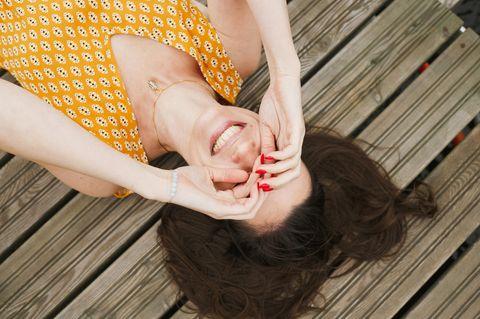 Lachende Frau liegt auf Steg mit Händen vor dem Gesicht