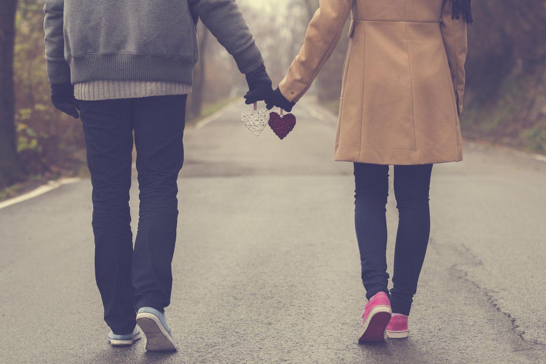 Was macht meinen Partner besonders? Ein Pärchen geht Hand in Hand, zwei Herzen haltend