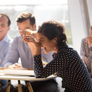 Frau sitzt lachend am Tisch